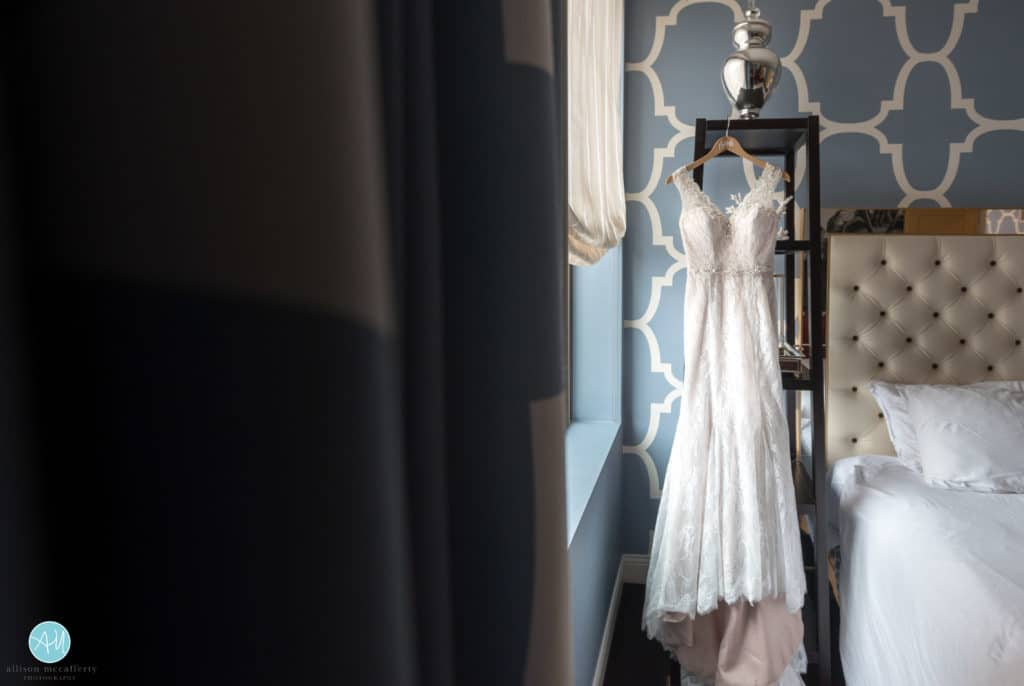 wedding dress hanging in window light