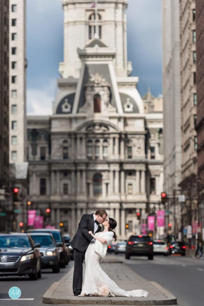 Bride and groom pose in front of Central Hall on Broad Street in Philadelphia