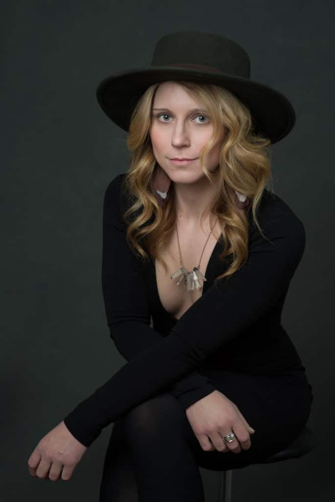 blonde model wearing a dark green hat, black v-neck long sleeved dress and crystal necklace for modern headshots in NJ