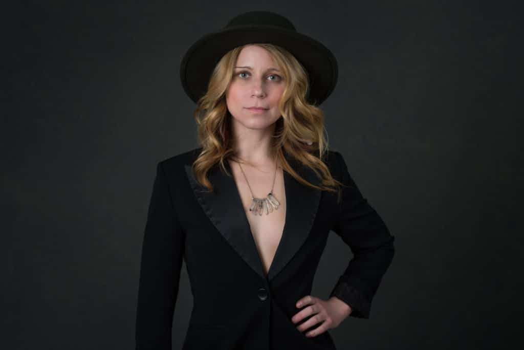 blonde model wearing a hat and tuxedo jacket with crystal necklace on a canvas backdrop in South Jersey photography studio.