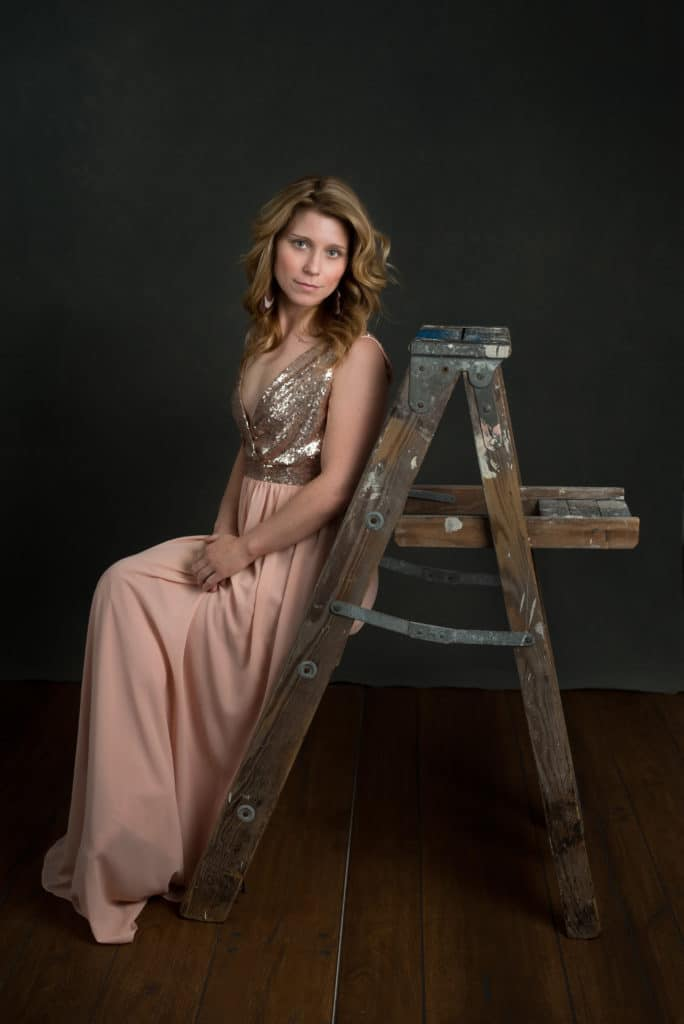 blonde model wearing a long pink sequin dress, sitting on a wood ladder in South Jersey portrait studio.