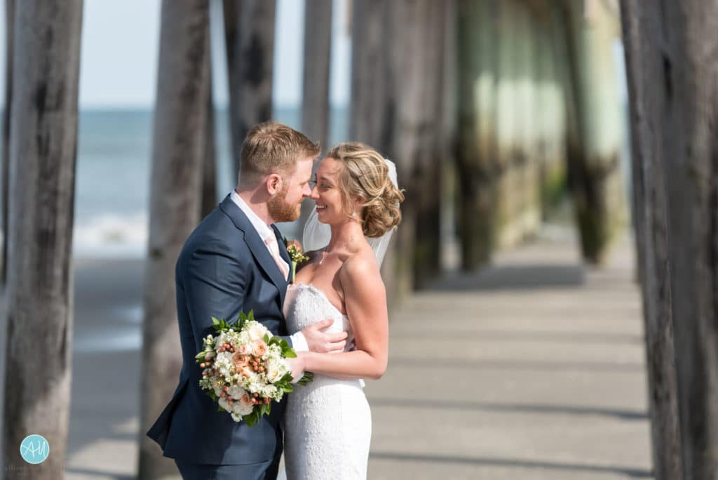 bride and groom under fishing pier avalon nj