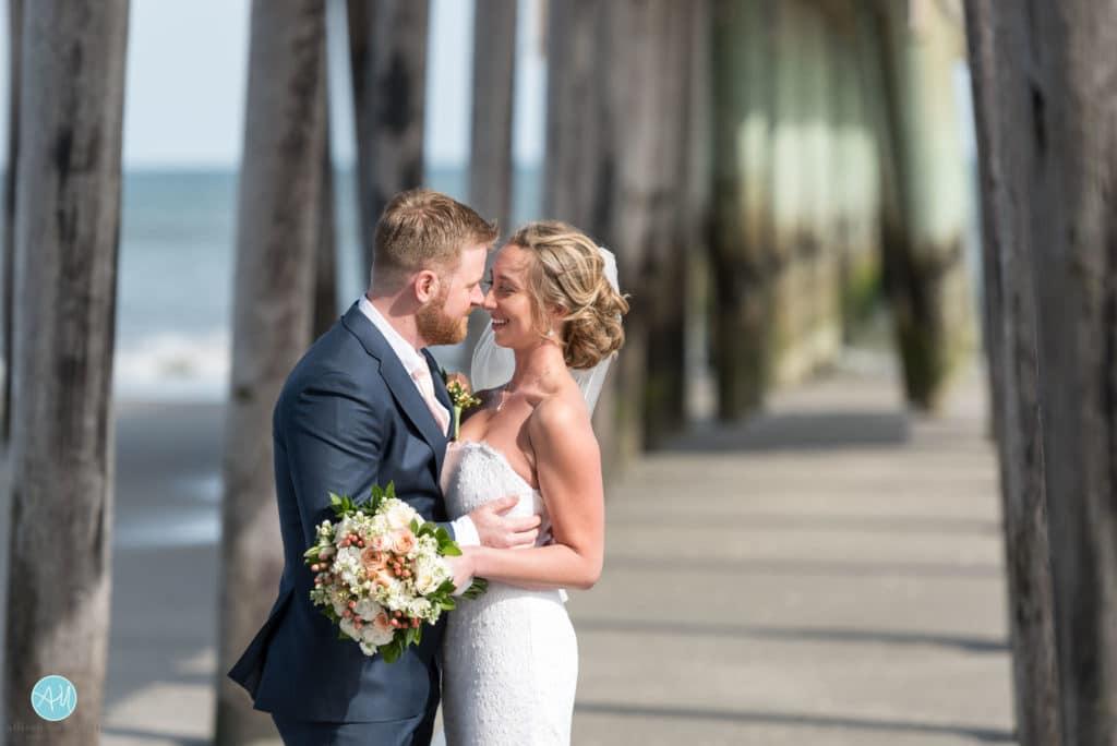bride and groom under fishing pier avalon nj
