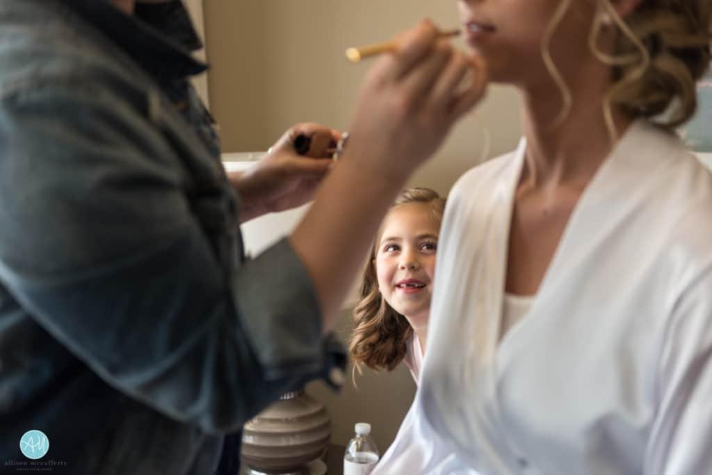 flower girl watching bride get makeup