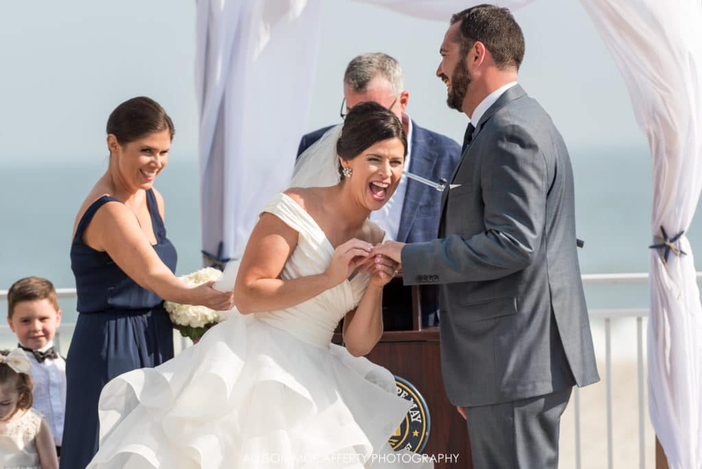 Bride laughing as she puts the ring on her husband