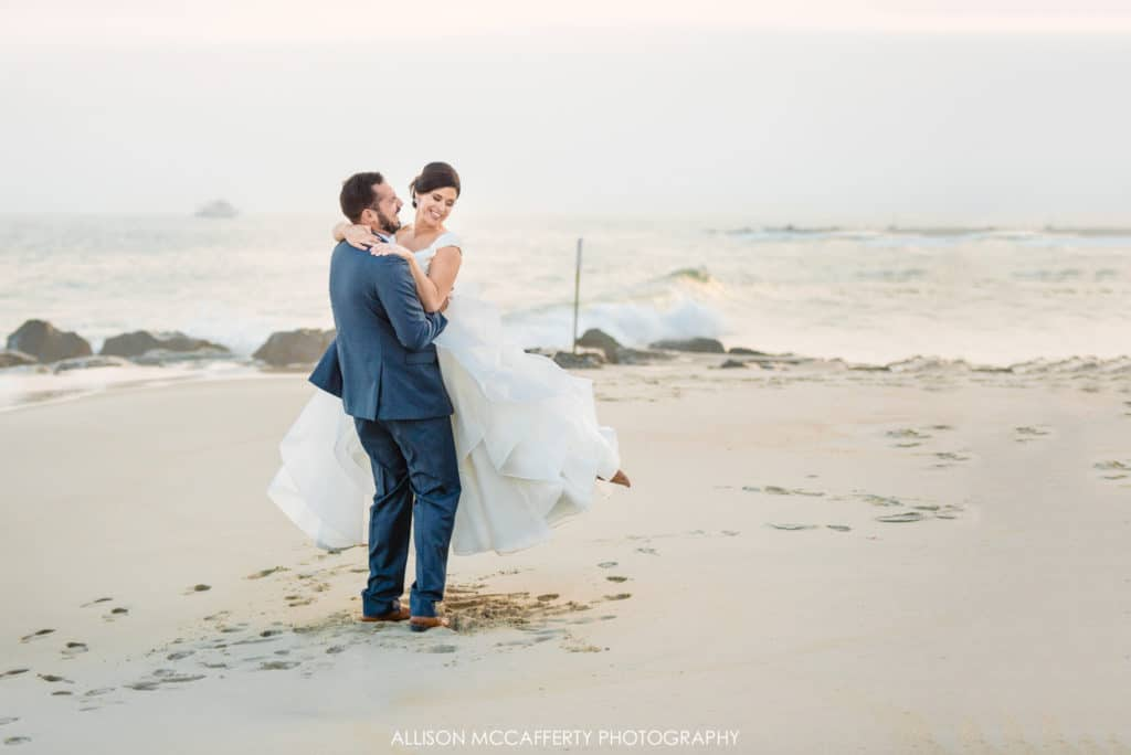 Groom twirling his wife on the beach in Cape May
