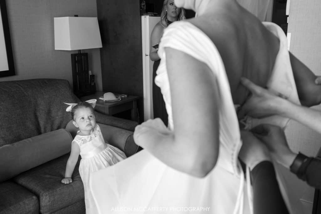 Flower girl watching bride get dressed