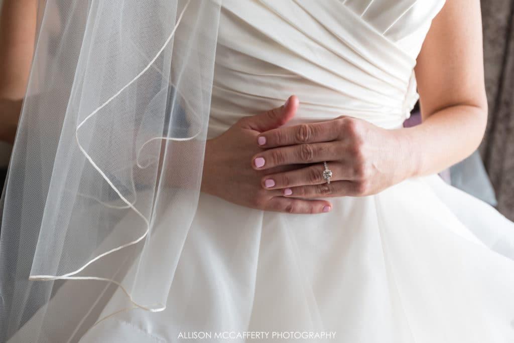 Bride's hands in front of wedding dress
