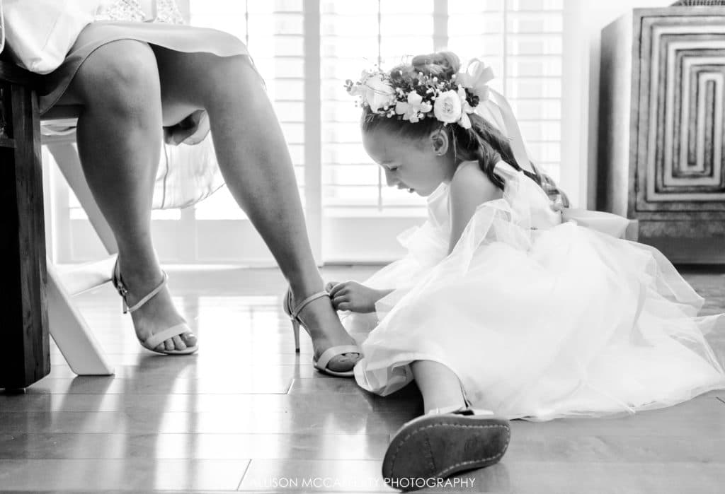 Flower girl helping her Mom put shoes on