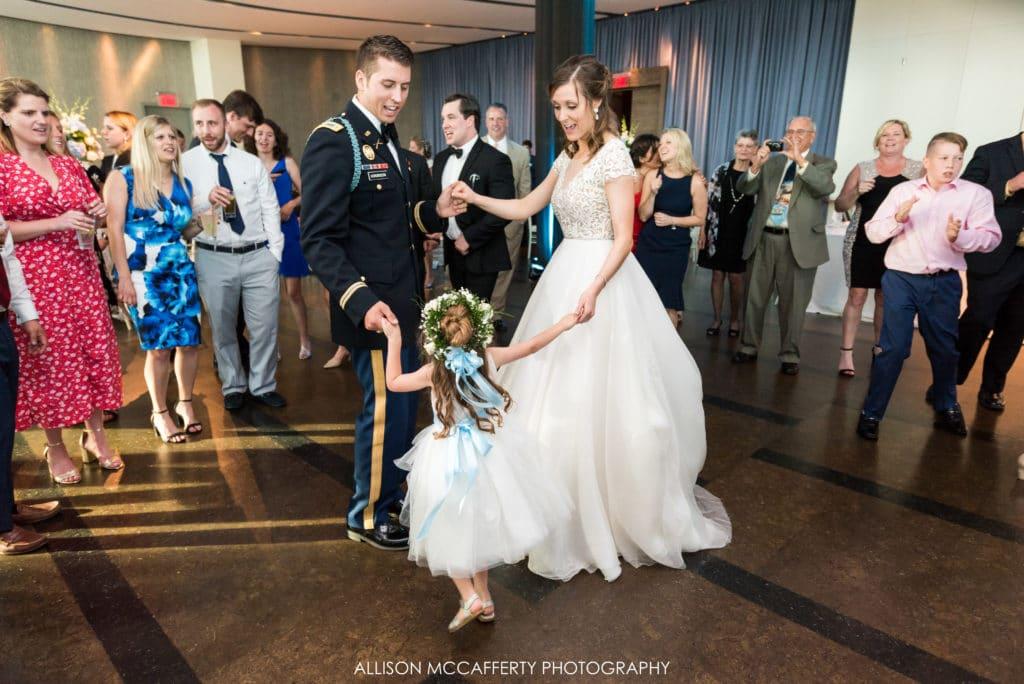 bride, groom and flower girl on the dance floor