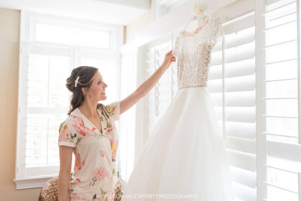 Bride admiring her wedding gown