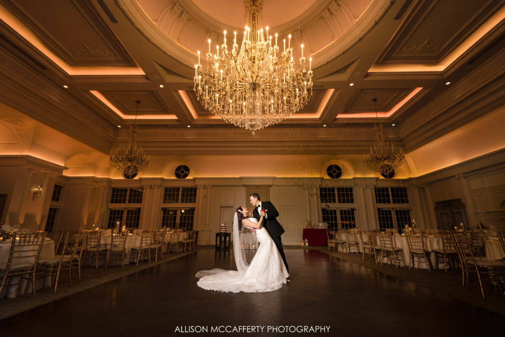 Bride and Groom dip on dance floor at the Park Chateau underneath the crystal chandelier