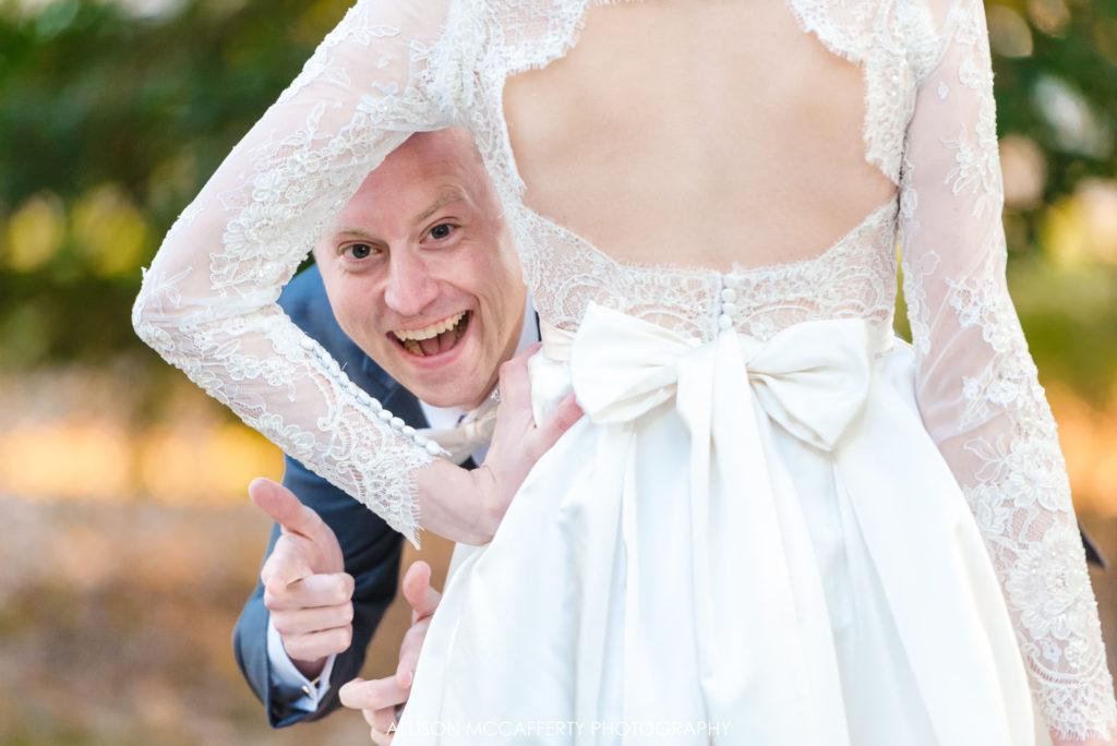 Groom peeking around bride