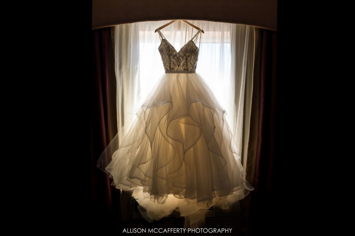 Wedding gown hanging in front of a window